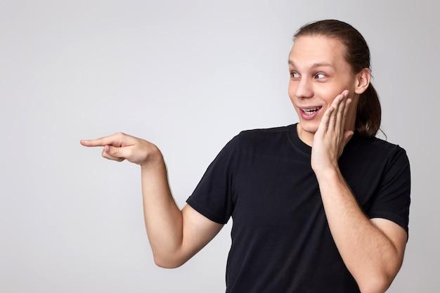 Удивленный молодой человек в черной футболке, указывая пальцем в сторону