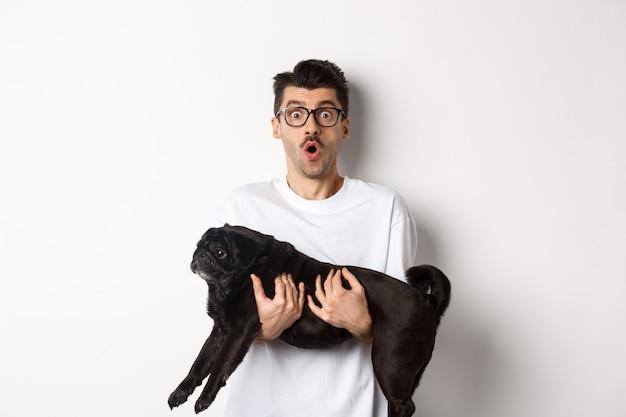 かわいい黒いパグを持って眼鏡をかけている驚いた若い男、印象的な顔でカメラを見つめている犬の飼い主は、すごい、白い背景の上に立って言って