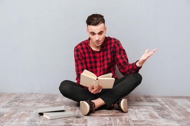 Удивлен молодой человек в рубашке, сидя на полу и читая книгу. изолированный серый фон
