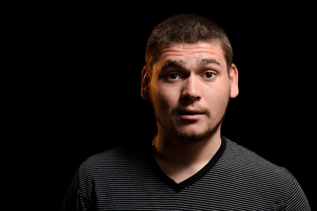 Surprised young man looking at camera isolated on dark background