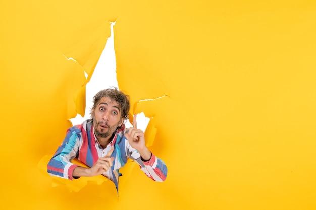 Il giovane sorpreso posa nel fondo strappato del foro di carta gialla