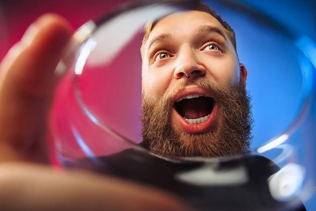 와인 한 잔 함께 포즈 놀된 젊은 남자. 감정적 인 남성 얼굴
