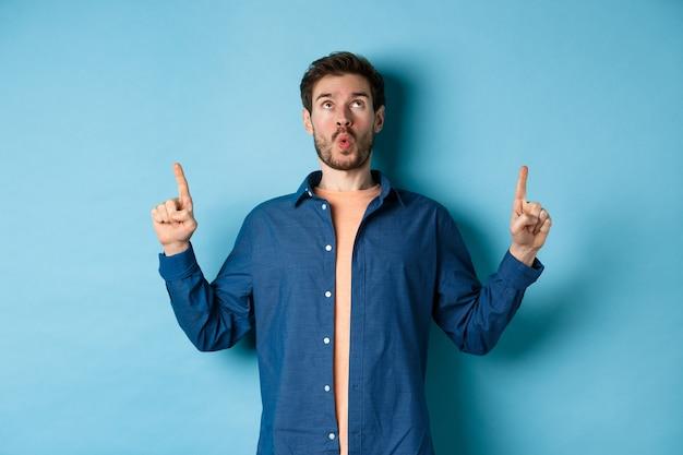 Удивленный молодой человек сказал ничего себе, глядя и указывая пальцами вверх на промо-предложение, стоя на синем фоне.