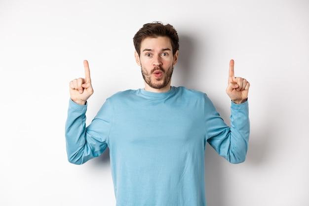 Удивленный молодой человек показывает верхнюю рекламу, указывая вверх и говорит вау на камеру, стоя на белом фоне.