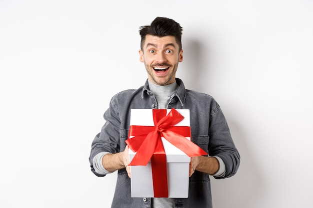 Surprised young man smiling excited, holding big gift box on valentines day holiday, receive surprise present, standing amazed on white.