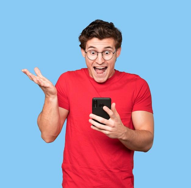 Удивленный молодой человек, использующий свой мобильный телефон
