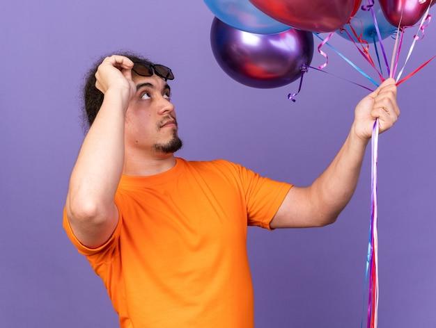 Удивленный молодой человек в очках держит и смотрит на воздушные шары