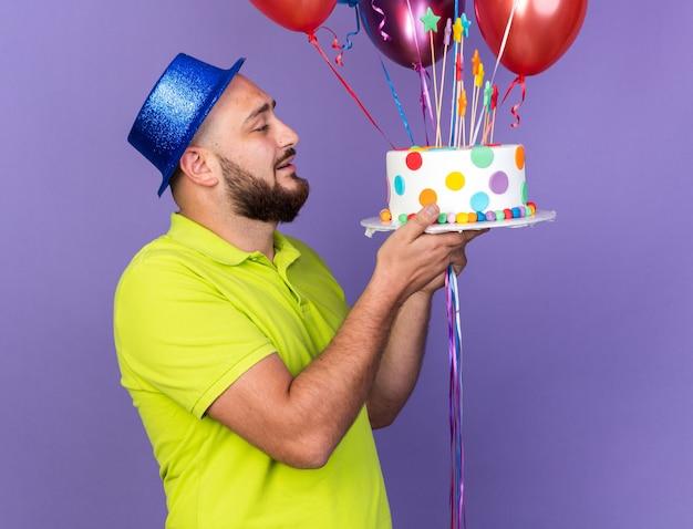 Giovane sorpreso che indossa un cappello da festa che tiene palloncini e guarda la torta in mano isolata sulla parete blu