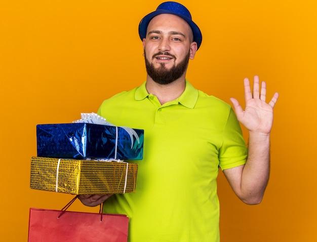 オレンジ色の壁に分離されたハロージェスチャーを示すバッグとギフトボックスを保持しているパーティーハットを身に着けている驚いた若い男
