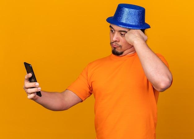 Giovane sorpreso che indossa un cappello da festa che tiene e guarda il telefono mettendo la mano sul tempio isolato sul muro arancione