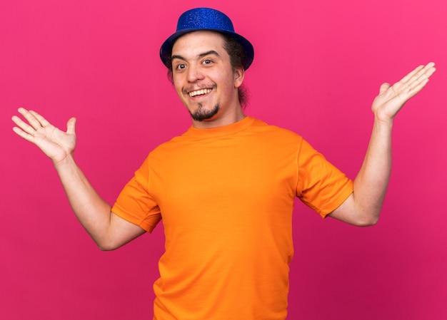 ピンクの壁に隔離された手を広げてパーティーハットを身に着けている驚いた若い男