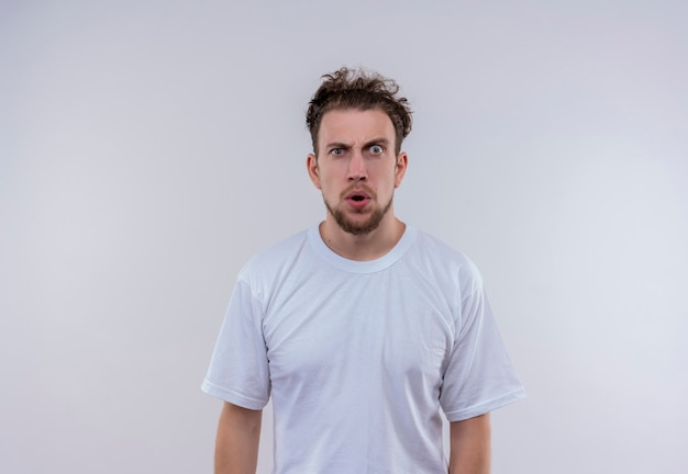 Surprised young man wearing white t-shirt on isolated white wall