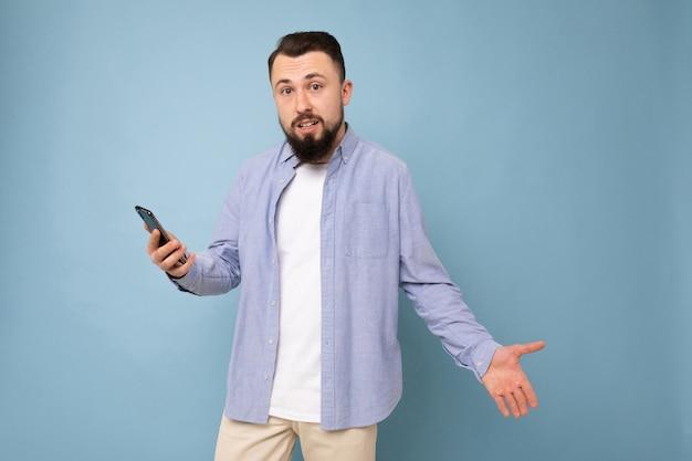 Удивленный молодой человек с телефоном в руках