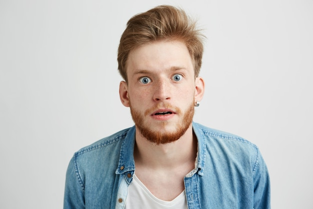 Surprised young man with beard in jean shirt looking stretching to camera.