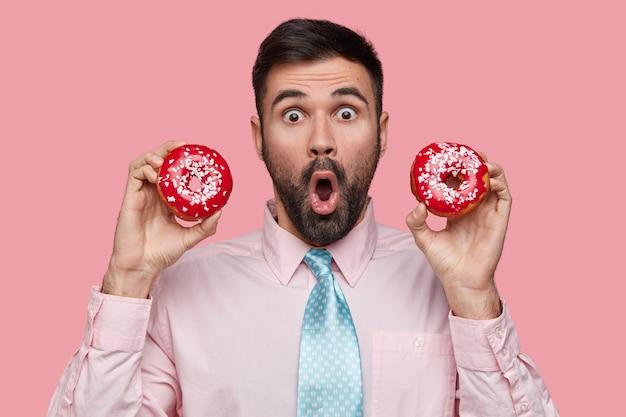 Giovane sorpreso con la barba scura, apre ampiamente la bocca, porta deliziose ciambelle, vestito in modo formale, isolato su uno spazio rosa