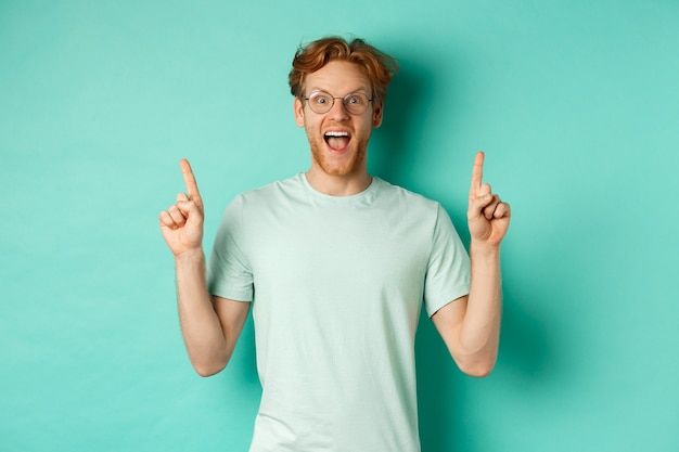 생강 머리를 한 젊은 남자, 안경과 티셔츠를 입고 경외심에 헐떡이며 프로모션 거래에서 손가락을 가리키며 민트 배경 위에 서 있습니다.