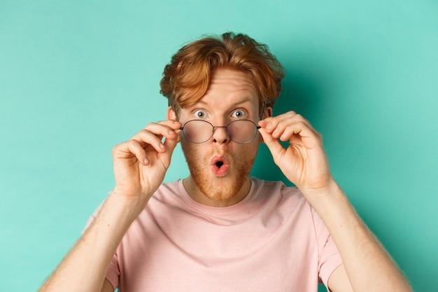 赤い髪の若い男を驚かせ、クールなものをチェックし、眼鏡を外し、ターコイズブルーの背景の上に立って、すごい感動したと言った