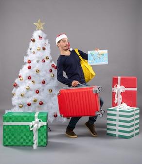 Удивленный молодой человек с желтым рюкзаком, держащий карту возле елки и подарки на сером