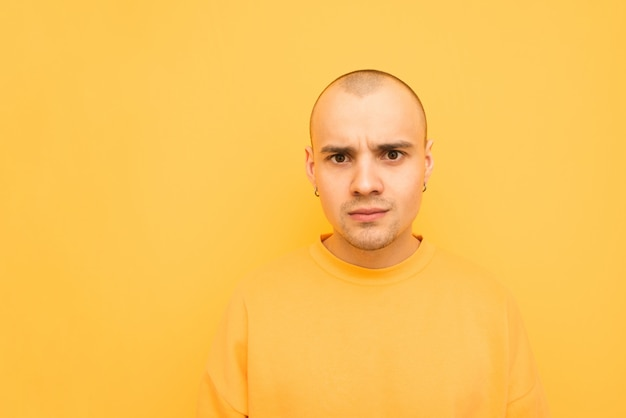 Surprised young man in a yellow overcoat stands on an orange and looks at the camera with a shocked face.