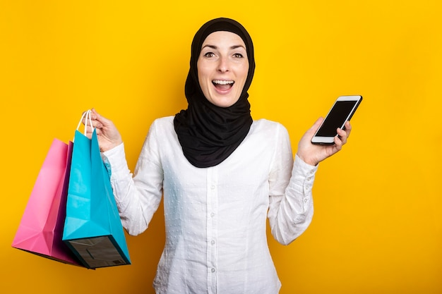Surprised young muslim woman in hijab holds shopping bags and phone on yellow