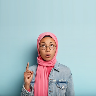 Surprised young muslim woman points up with one fore finger, focused upwards, has concerned facial expression, veiled head