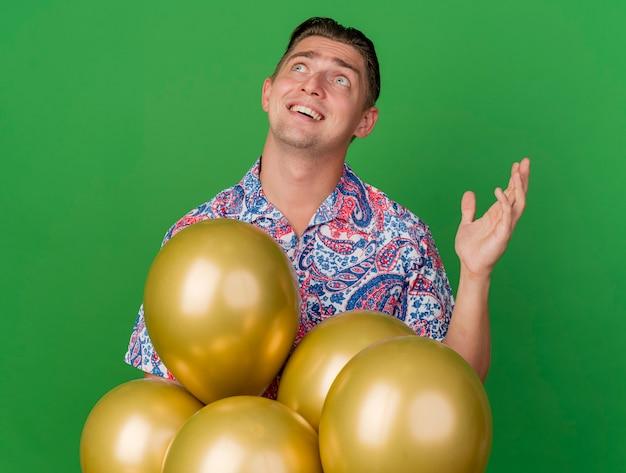 Ragazzo giovane sorpreso del partito che esamina su che porta la camicia variopinta che sta dietro i palloni che sollevano la mano isolata sul verde