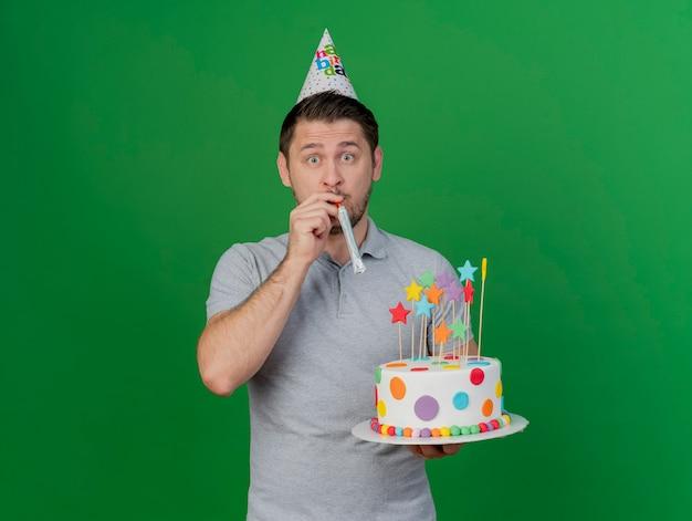 誕生日の帽子をかぶって笛を吹いて、緑に分離されたケーキを持って驚いた若いパーティーの男