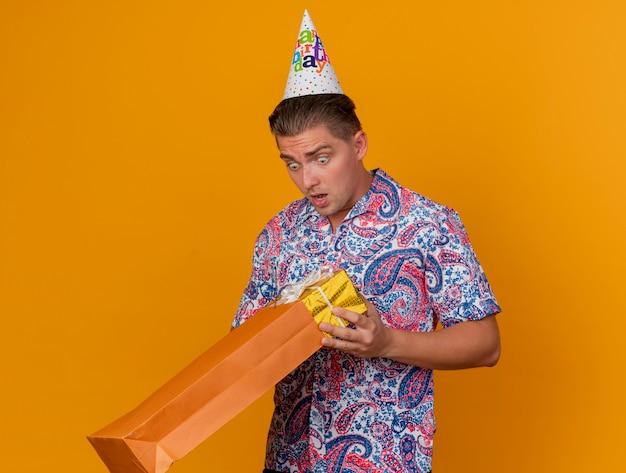 생일 모자를 쓰고 오렌지에 고립 된 선물 가방을보고 놀란 젊은 파티 남자