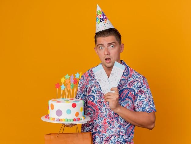 オレンジ色に分離されたケーキとチケットのギフトバッグを保持している誕生日の帽子をかぶって驚いた若いパーティーの男