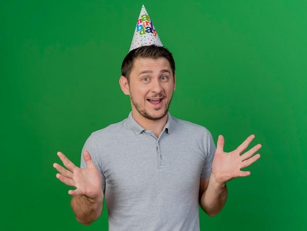 Удивленный молодой тусовщик в шапочке для дня рождения, разводя руками, изолированными на зеленом