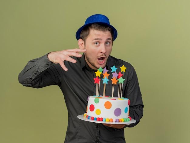 올리브 그린에 고립 된 케이크를 들고 검은 셔츠와 파란색 모자를 쓰고 놀란 된 젊은 파티 남자