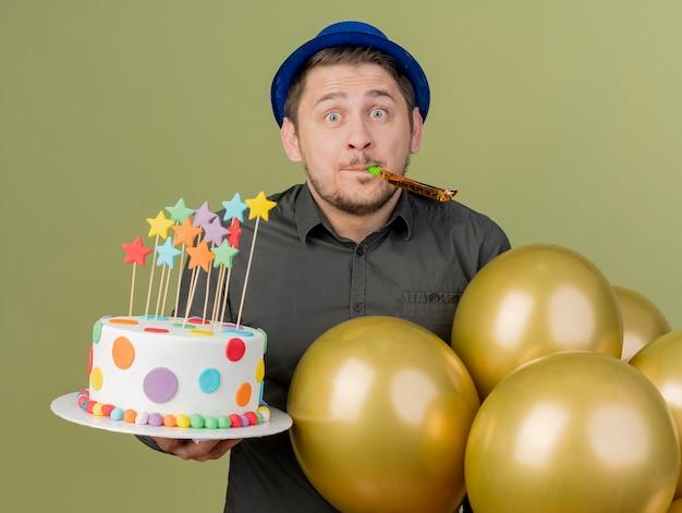 올리브 그린에 고립 된 휘파람을 불고 풍선과 함께 케이크를 들고 검은 셔츠와 파란색 모자를 입고 놀란 젊은 파티 남자