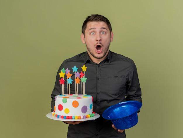 올리브 그린에 고립 된 파란색 모자와 케이크를 들고 검은 셔츠를 입고 놀란 된 젊은 파티 남자