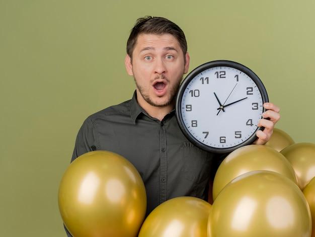 올리브 그린에 고립 된 벽 시계를 들고 풍선 가운데 서있는 검은 셔츠를 입고 놀란 된 젊은 파티 남자