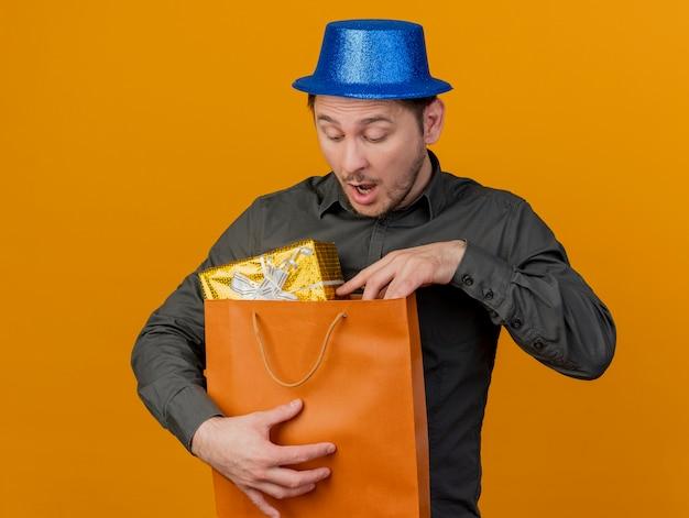 파란색 모자를 쓰고 오렌지에 고립 된 선물 가방을보고 놀란 젊은 파티 남자