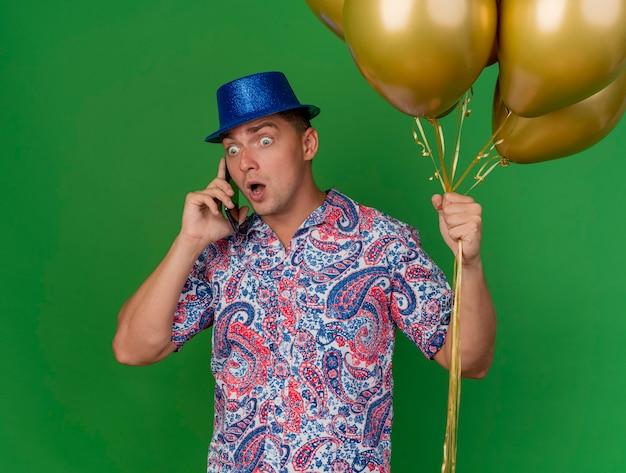 풍선을 들고 파란색 모자를 쓰고 놀란 된 젊은 파티 남자는 녹색 배경에 고립 된 전화에 말한다