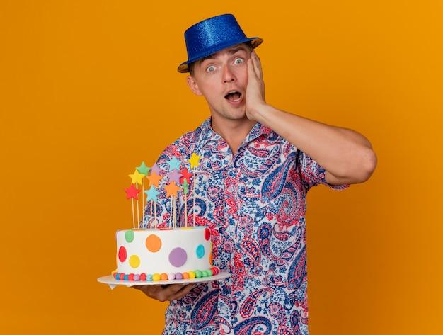 케이크를 들고 오렌지에 고립 된 뺨에 손을 넣어 파란색 모자를 쓰고 놀란 젊은 파티 남자
