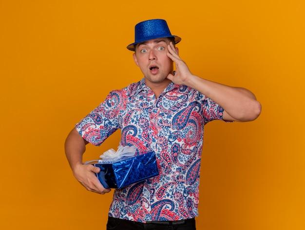 ギフトボックスを保持し、オレンジ色に分離された頬に手を置く青い帽子をかぶって驚いた若いパーティーの男