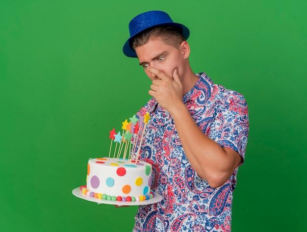 Ragazzo giovane sorpreso del partito che porta la tenuta blu del cappello e che esamina la torta che mette la mano sulla bocca isolata sul verde