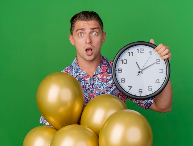 Ragazzo giovane partito sorpreso che indossa la camicia colorata in piedi dietro i palloncini e tenendo l'orologio da parete isolato sul verde