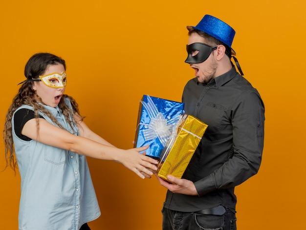 오렌지에 고립 된 그의 손에 선물에 손을 들고 가장 무도회 아이 마스크 소녀를 입고 놀란 젊은 파티 남자