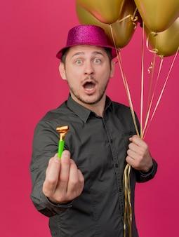 Удивленный молодой тусовщик в розовой шляпе с воздушными шарами и вентилятором, изолированным на розовом