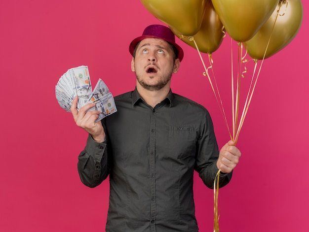 Surprised young party guy  wearing pink hat holding balloons with cash isolated on pink Free Photo