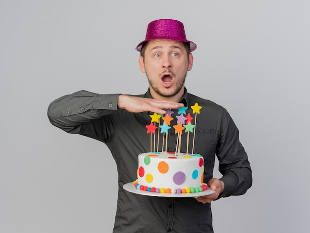 흰색 배경에 고립 된 케이크를 들고 분홍색 모자를 쓰고 놀란 된 젊은 파티 남자