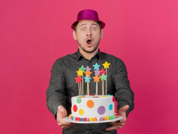 Ragazzo giovane partito sorpreso che porta il cappello dentellare che tiene fuori la torta isolata sul colore rosa