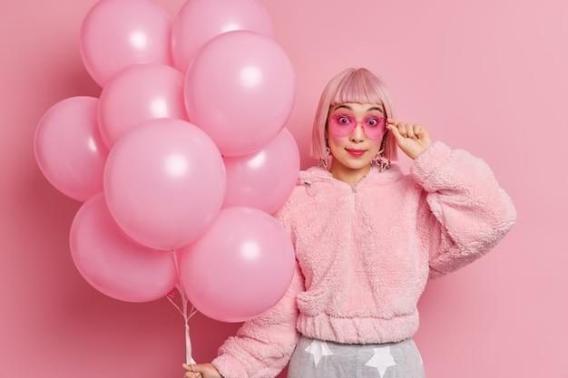 Giovane donna abbastanza asiatica sorpresa con i capelli rosa