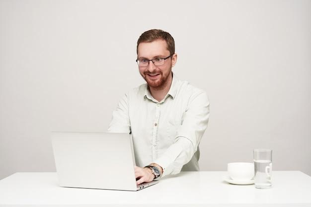 Giovane maschio biondo piuttosto barbuto sorpreso con gli occhiali guardando eccitato lo schermo del suo computer portatile durante la lettura di notizie inaspettate, in posa su sfondo bianco