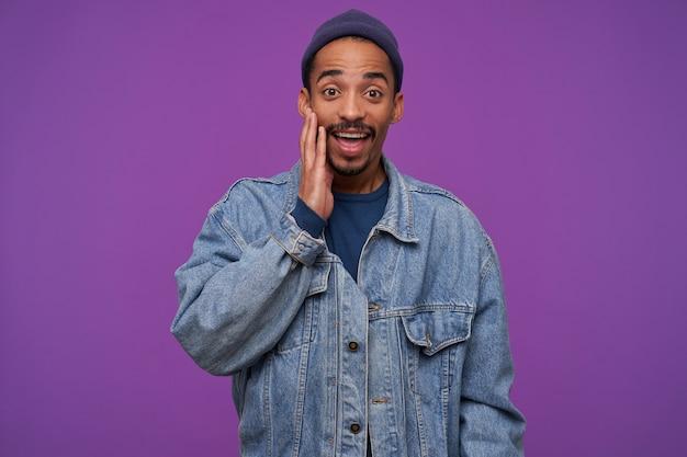 Giovane uomo barbuto dalla pelle scura dagli occhi marroni sorpreso che tiene il palmo sollevato sulla guancia mentre guarda meravigliato, in piedi sul muro viola