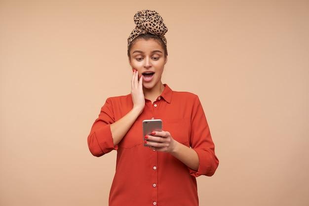 Удивленная молодая симпатичная шатенка с естественным макияжем изумленно смотрит на экран своего телефона и держит руку на лице, изолированном над бежевой стеной