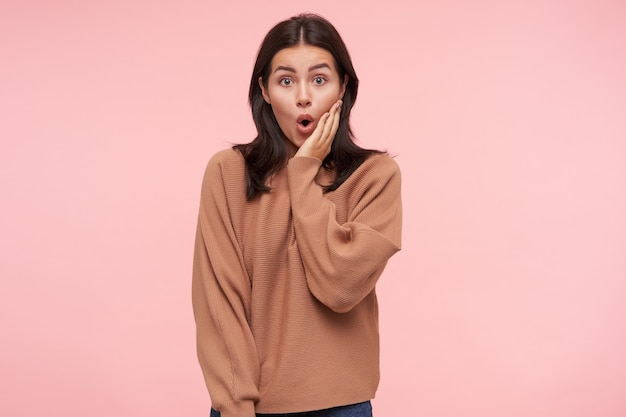 Surprised young pretty brunette woman with loose hair holding raised palm on her cheek while looking amazedly at front with wide eyes opened, isolated over pink wall